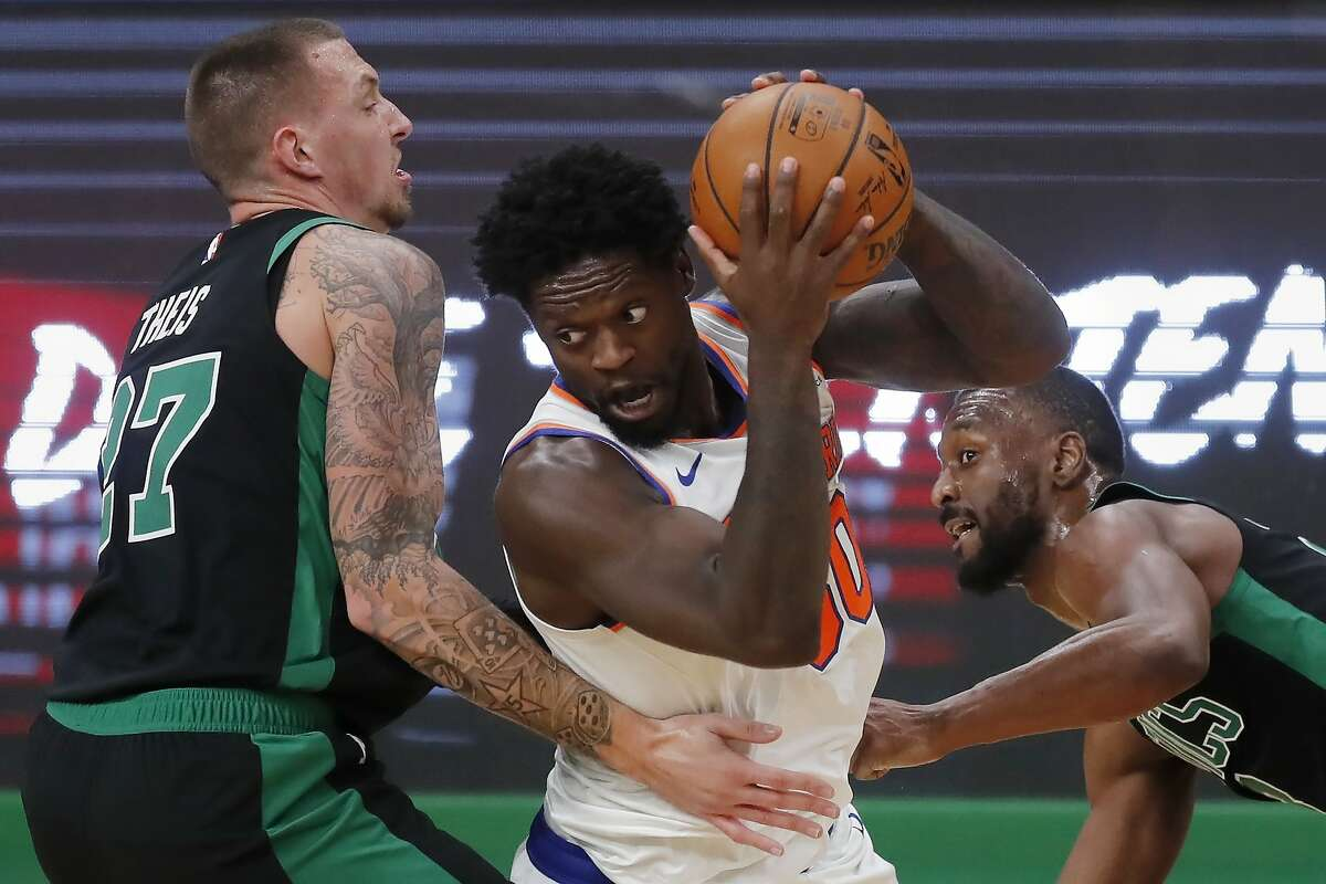 Boston Celtics' Daniel Theis (27) and Kemba Walker defend against New York Knicks' Julius Randle (30) during the second half of an NBA basketball game, Sunday, Jan. 17, 2021, in Boston. (AP Photo/Michael Dwyer)