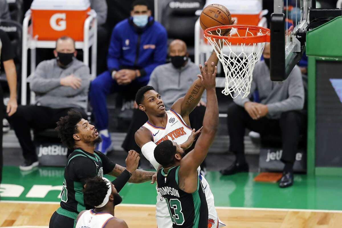 New York Knicks' RJ Barrett shoots against Boston Celtics' Marcus Smart (36) and Tristan Thompson (13) during the first half of an NBA basketball game, Sunday, Jan. 17, 2021, in Boston. (AP Photo/Michael Dwyer)