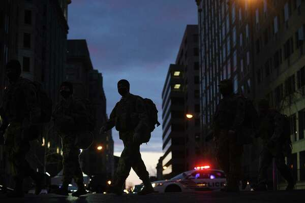 National Guard troops march through the downtown area of Washington on Sunday, Jan. 17, 2021.