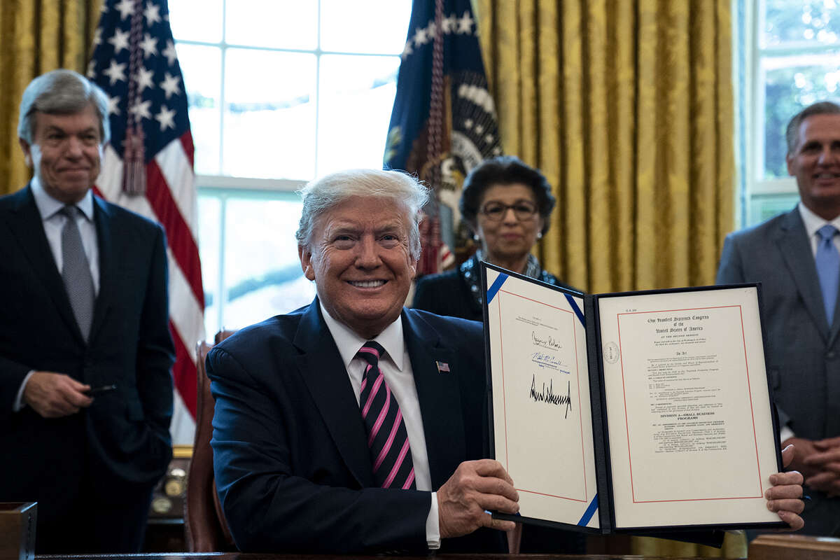 President Donald Trump smiles holding up his signed H.R.266, the Paycheck Protection Program and Health Care Enhancement bill, in the Oval Office of the White House in Washington DC on April 24th, 2020. (Pool/Abaca Press/TNS)