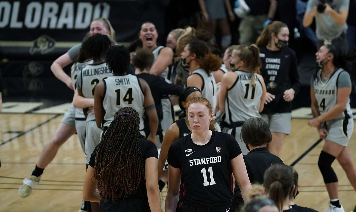 Stanford guard Haley Jones, front left, consoles Stanford forward Ashten Prechtel, front right, as Colorado players celebrate Sunday's overtime defeat of the previously unbeaten Cardinal.