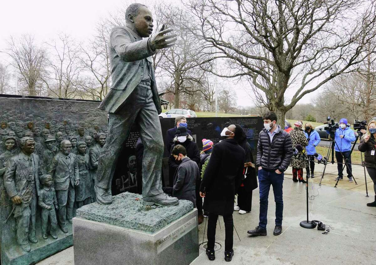 Albany County Legislator Beroro Efekoro looks up at the Dr. Martin Luther King, Jr. statue in Lincoln Park during a wreath laying ceremony on Monday, Jan. 18, 2021, in Albany, N.Y. (Paul Buckowski/Times Union)