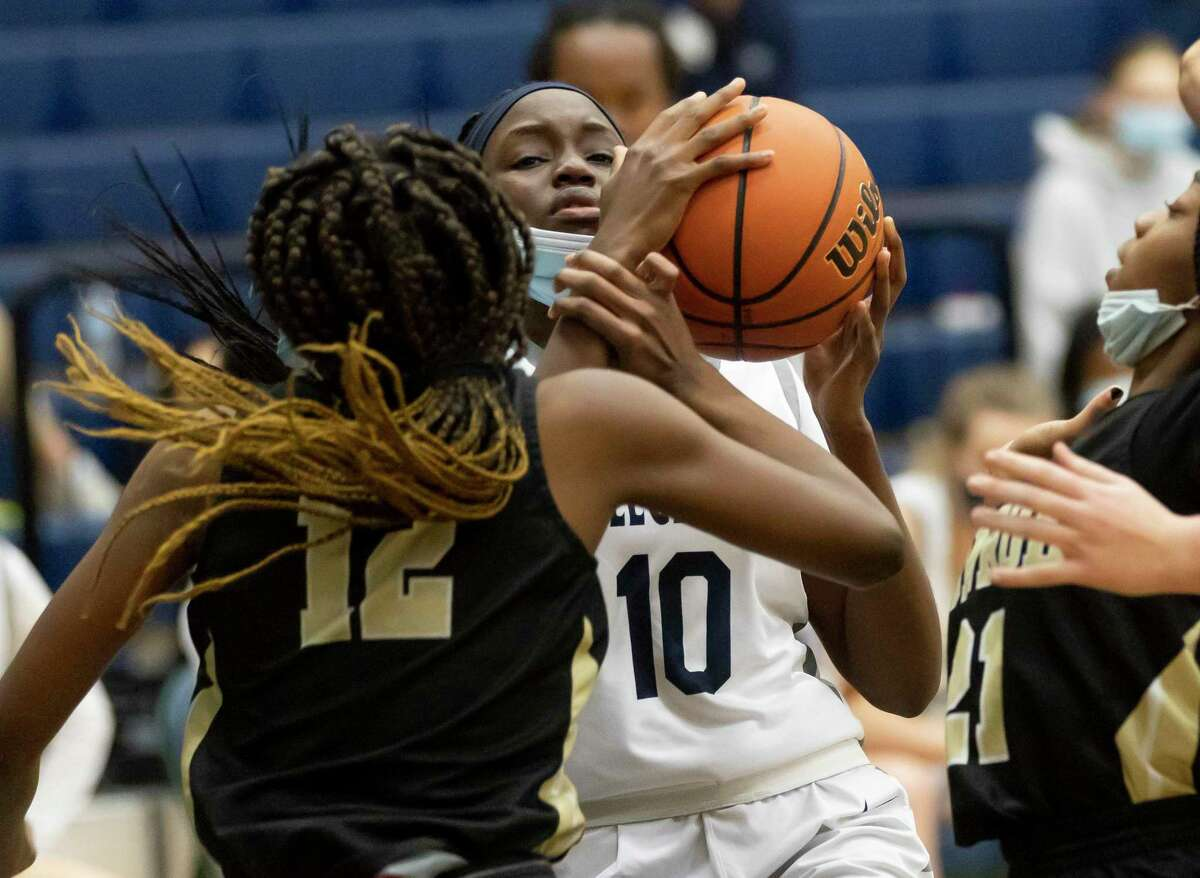 College Park power forward Ali Diop (10) pushes through Conroe Tiarra Howard (12) in order to pass the ball during the fourth quarter of a District 13-6A girls basketball game at College Park High School, Saturday, Jan. 16, 2021, in The Woodlands.