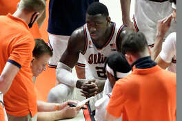 Illinois center Kofi Cockburn (21) listens to head coach Brad Underwood during a timeout against Ohio State in the second half of an NCAA college basketball game Saturday, Jan. 16, 2021, in Champaign, Ill.
