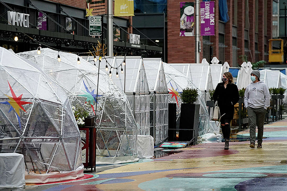 People walk by outdoor plastic dining bubbles and restaurants that were prohibited from indoor service tried to attract customers as temperatures turned colder.