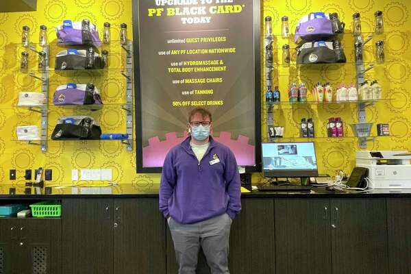 Trainer Jimmy Hollars, 26, stands behind the front desk at Planet Fitness during a recent shift and welcomes gym-goers. Hollars said by learning about preventative health and other methods of training, he is able to work with clients and assist them in developing fitness goals that are specific to them. (Pioneer photo/Bradley Massman)