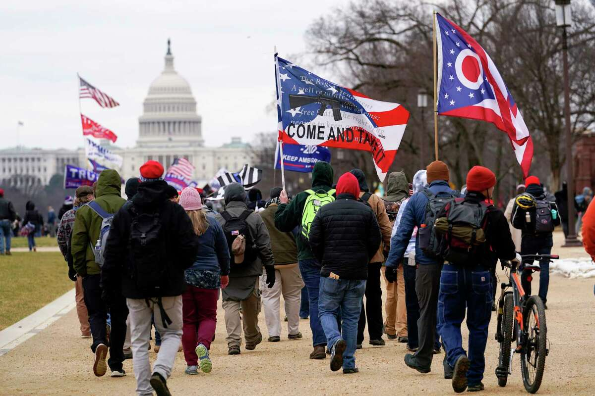 In this Wednesday, Jan. 6, 2021, file photo, supporters of President Donald Trump march towards the Capitol holding flags during rally in Washington. War-like imagery has begun to take hold in mainstream Republican political circles in the wake of the deadly attack on the U.S. Capitol, with some elected officials and party leaders rejecting calls to tone down their rhetoric contemplating a second civil war. (AP Photo/Carolyn Kaster, File)