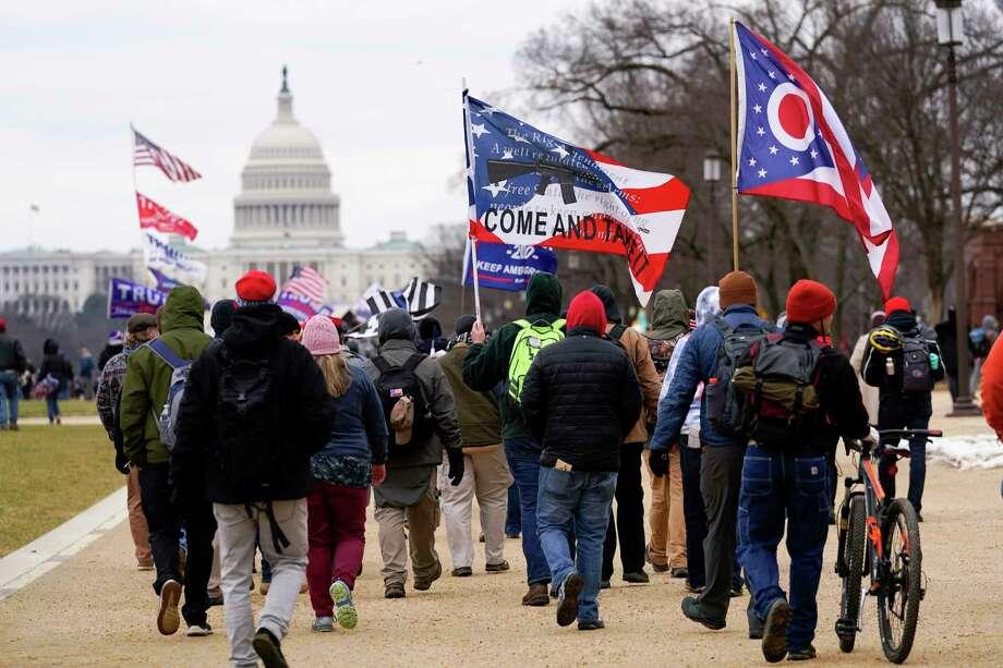 In this Wednesday, Jan. 6, 2021, file photo, supporters of President Donald Trump march towards the Capitol holding flags during rally in Washington. War-like imagery has begun to take hold in mainstream Republican political circles in the wake of the deadly attack on the U.S. Capitol, with some elected officials and party leaders rejecting calls to tone down their rhetoric contemplating a second civil war. (AP Photo/Carolyn Kaster, File) / Copyright 2021 The Associated Press. All rights reserved