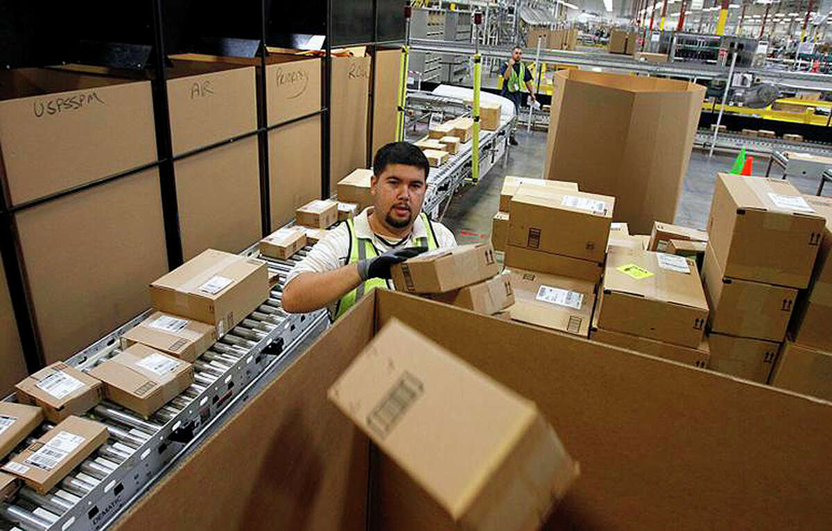 Ricardo Sandoval places packages in the right shipping boxes at an Amazon.com fulfillment center.