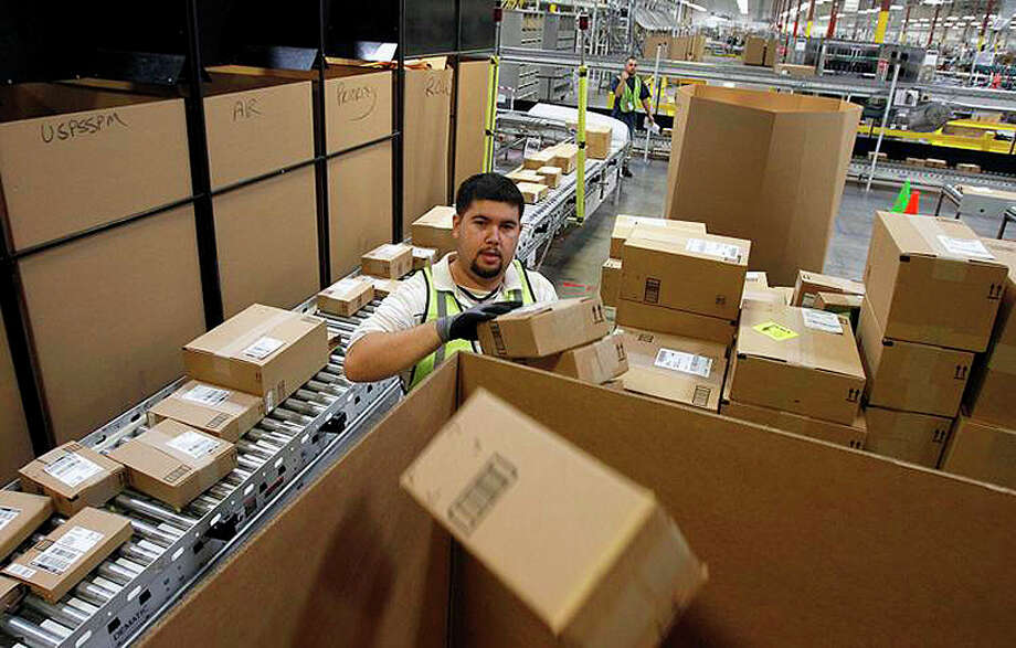 Ricardo Sandoval places packages in the right shipping boxes at an Amazon.com fulfillment center. Photo: Ross D. Franklin | AP