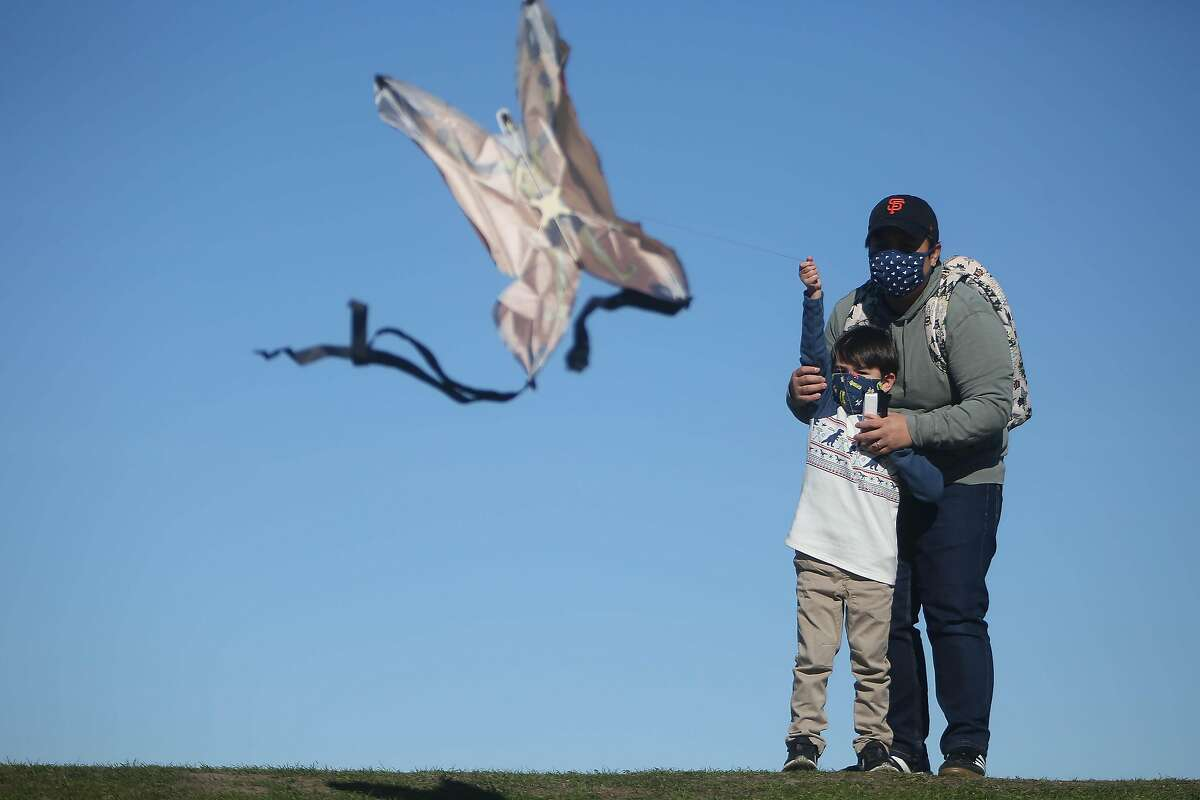 Lorraine Esturas-Pierson (right) and her son Wilder Esturas-Pierson (left), 4, both of Emeryville, fly their kite on top of a hill at at C�sar E. Ch�vez Park on Monday, January 18, 2021 in Berkeley, Calif. On Monday, Wilder was able to fly a kite for the first time after an unsuccsessful attempt at the park the day before. The National Weather Service issues a high wind advisory on Monday with high winds continuing until Tuesday.
