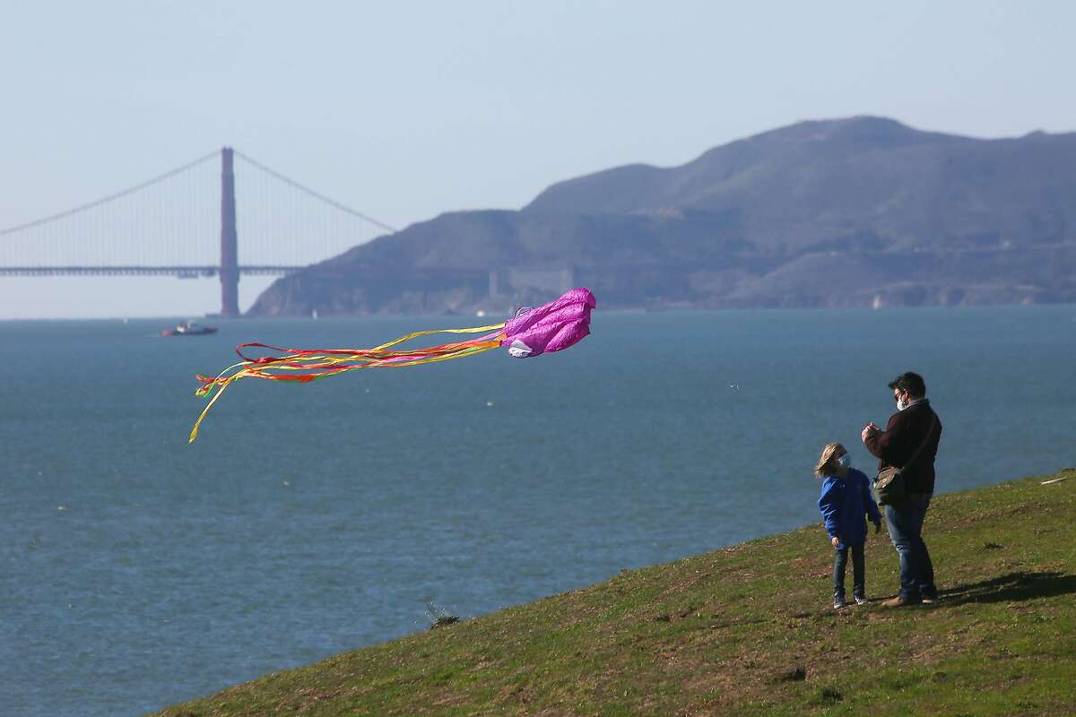 Adam Gerardin (right) and his daughter Nia Gerardin (left), 6, both of Richmond, fly their kite from the top of a hill at at C�sar E. Ch�vez Park on Monday, January 18, 2021 in Berkeley, Calif. The National Weather Service issues a high wind advisory on Monday with high winds continuing until Tuesday.