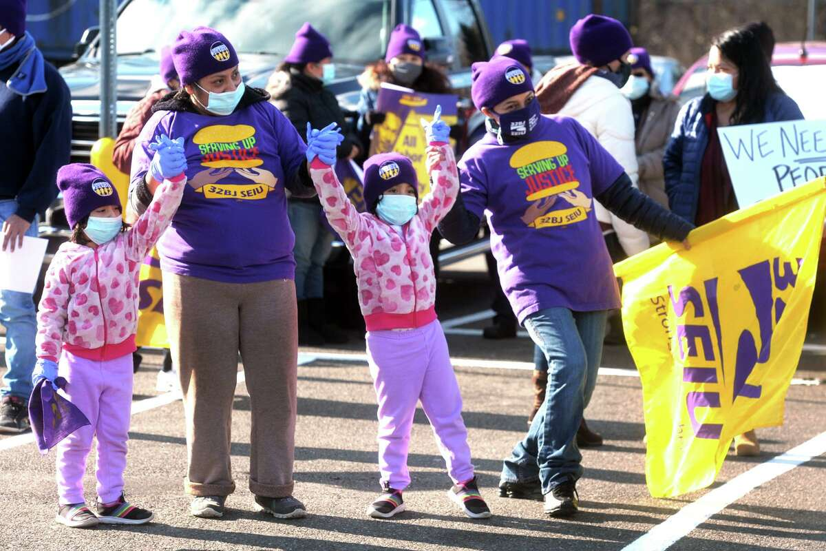 Azucena Santiago, left, who works at one of the Milford Service Plaza McDonald's, cheers with her family during a rally at the northbound Fairfield Service Plaza, in Fairfield, Conn. Jan. 18, 2021. About a hundred service plaza workers gathered in honor of Martin Luther King Jr. Day and to speak about their rights.
