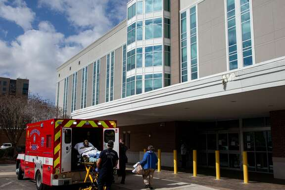 A patient is transported by ambulance from the Heights Hospital on Monday, Jan. 18, 2021, in Houston. The hospital has filed for bankruptcy, leaving medical staff and patients locked out without any notice.
