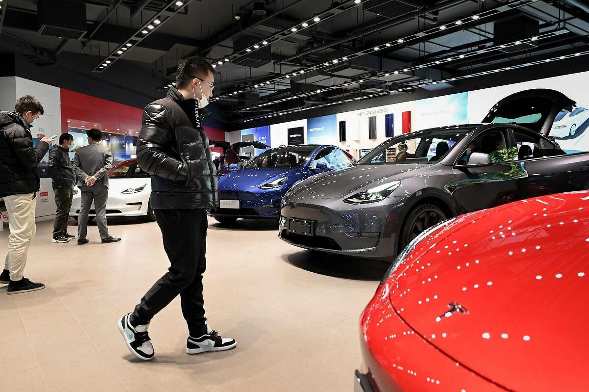 People look at a Tesla Model Y car at a Tesla showroom in Beijing on Jan. 5.