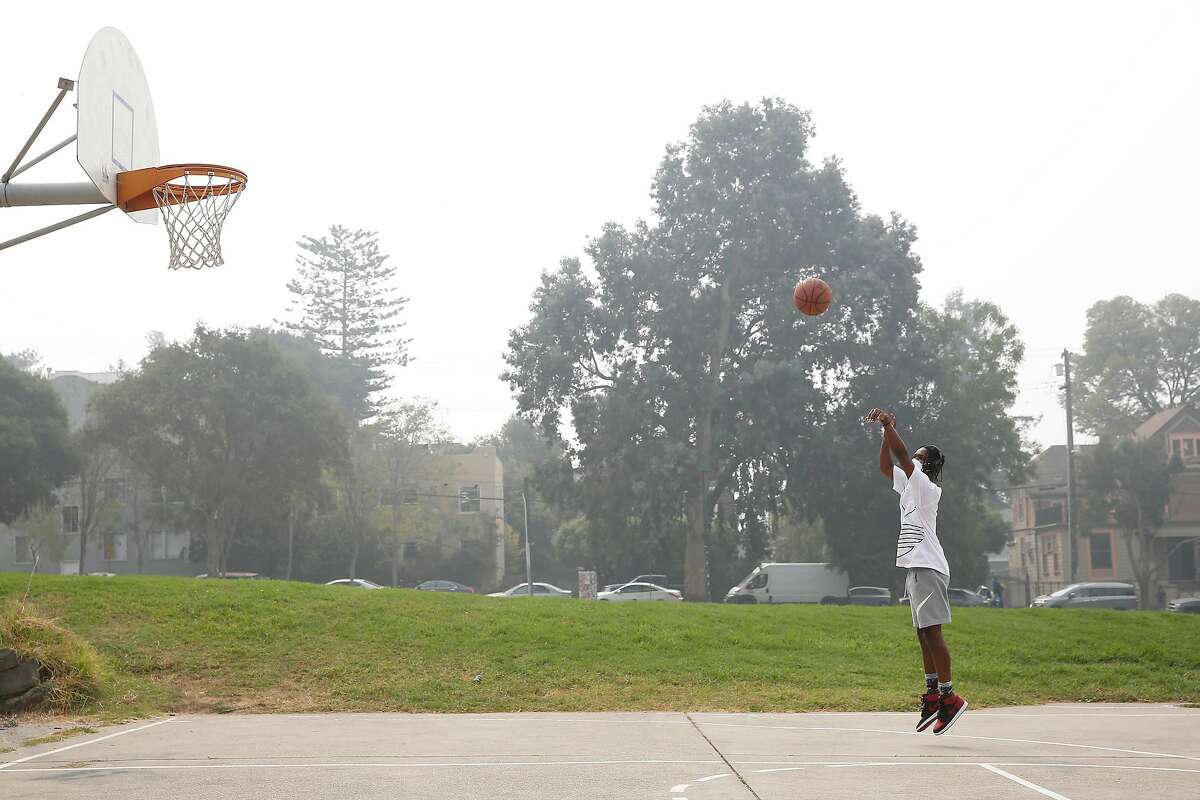 Marcus Sikora of Berkeley shoots some baskets at the court at People's Park while behind him is seen haze due to wildfires on Friday, September 11, 2020 in Berkeley, Calif.