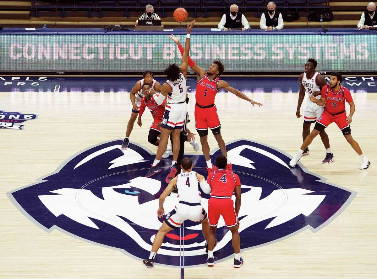 UConn's Isaiah Whaley (5) and St. John's Josh Roberts (1) jump for the tip-off to start an NCAA college basketball game in Storrs, Connecticut, Monday, Jan. 18, 2021. (David Butler II/Pool photo via AP)