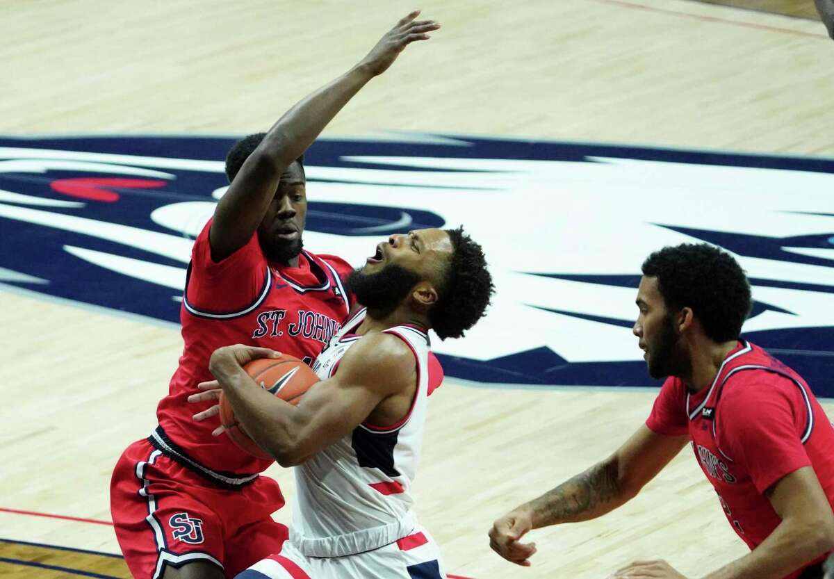 UConn guard R.J. Cole, center, drives against St. John's Greg Williams Jr., left, during the first half of an NCAA college basketball game in Storrs, Connecticut, Monday, Jan. 18, 2021. (David Butler II/Pool photo via AP)