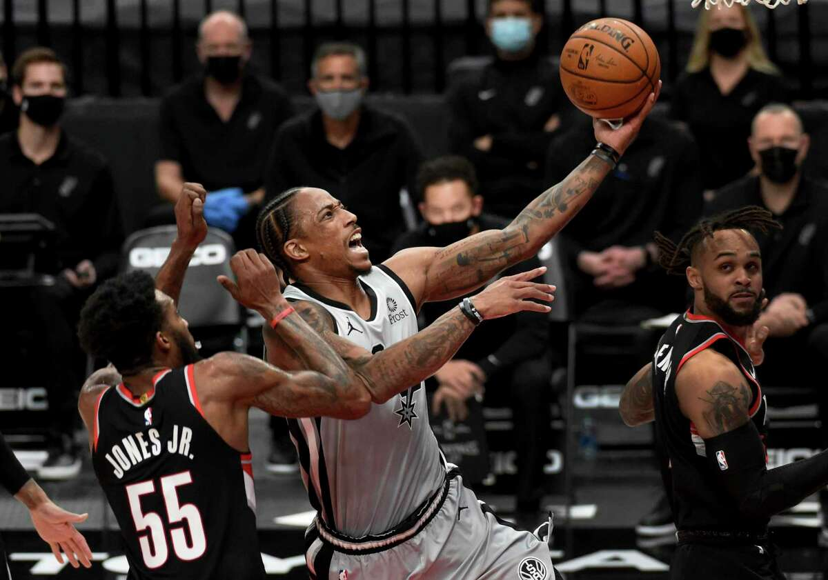 The Spurs' DeMar DeRzona drives past the Trail Blazers' Derrick Jones Jr. in the second half for two of his 20 points Monday at the Moda Center in Portland, Ore. DeRozan also tied with Dejounte Murray for the team lead with 11 assists.