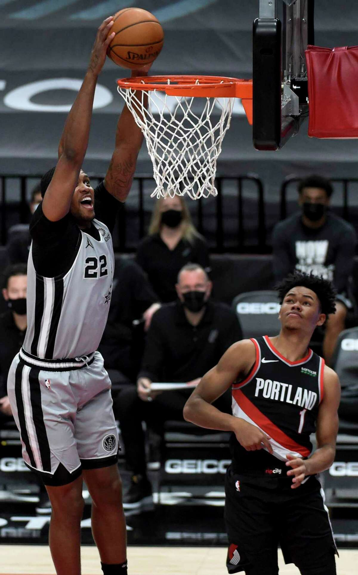Rudy Gay throws down a dunk for the Spurs in front of the Trail Blazers' Anfernee Simons on Monday in Portland. Gay contributed 21 points off the bench, hitting 5 of 8 3-pointers.