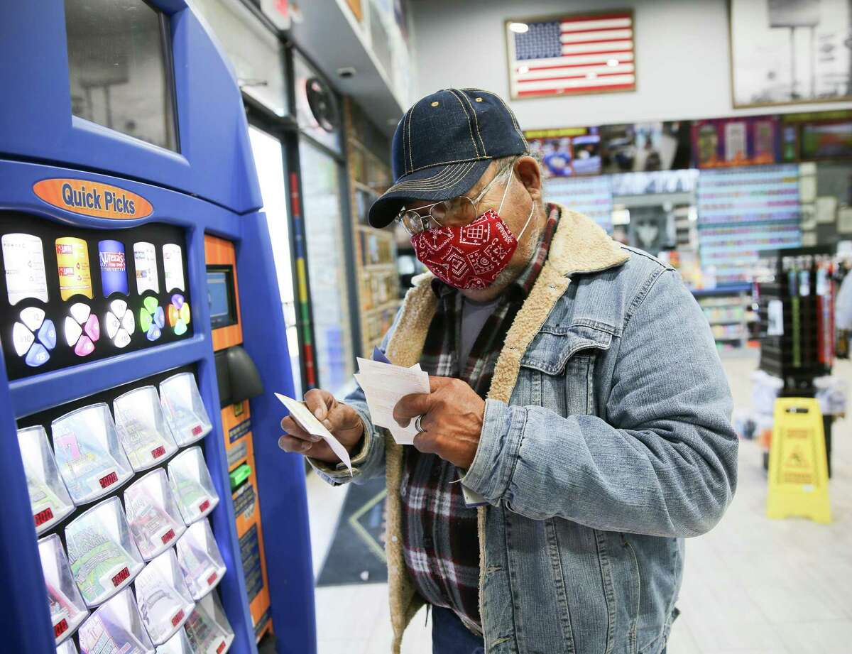 A hopefully lottery player checks his old tickets before buying more at Lucky Rudy's in Rosenberg, Texas on Wednesday, Jan. 13, 2021.