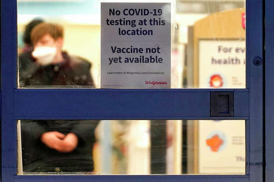 An informational sign that COVID-19 vaccines are not yet available greets customers at a Walgreens. Photo: Nam Y. Huh | AP