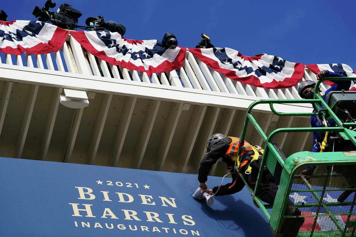 Unos trabajadores instalan unos banderines afuera de la Casa Blanca el lunes 18 de enero de 2021, en Washington, durante los preparativos para la ceremonia de investidura del presidente electo Joe Biden y de la vicepresidenta electa Kamala Harris.