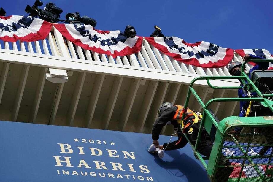 Unos trabajadores instalan unos banderines afuera de la Casa Blanca el lunes 18 de enero de 2021, en Washington, durante los preparativos para la ceremonia de investidura del presidente electo Joe Biden y de la vicepresidenta electa Kamala Harris. Photo: John Minchillo /Associated Press / Copyright 2021 The Associated Press. All rights reserved.