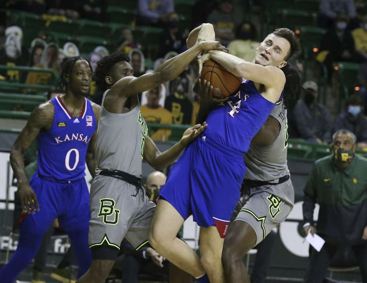 Kansas forward Mitch Lightfoot, right, pulls down a rebound over Baylor guard Adam Flagler, left, in the first half of an NCAA college basketball game, Monday, Jan. 18, 2021, in Waco, Texas. (Rod Aydelotte/Waco Tribune-Herald via AP)