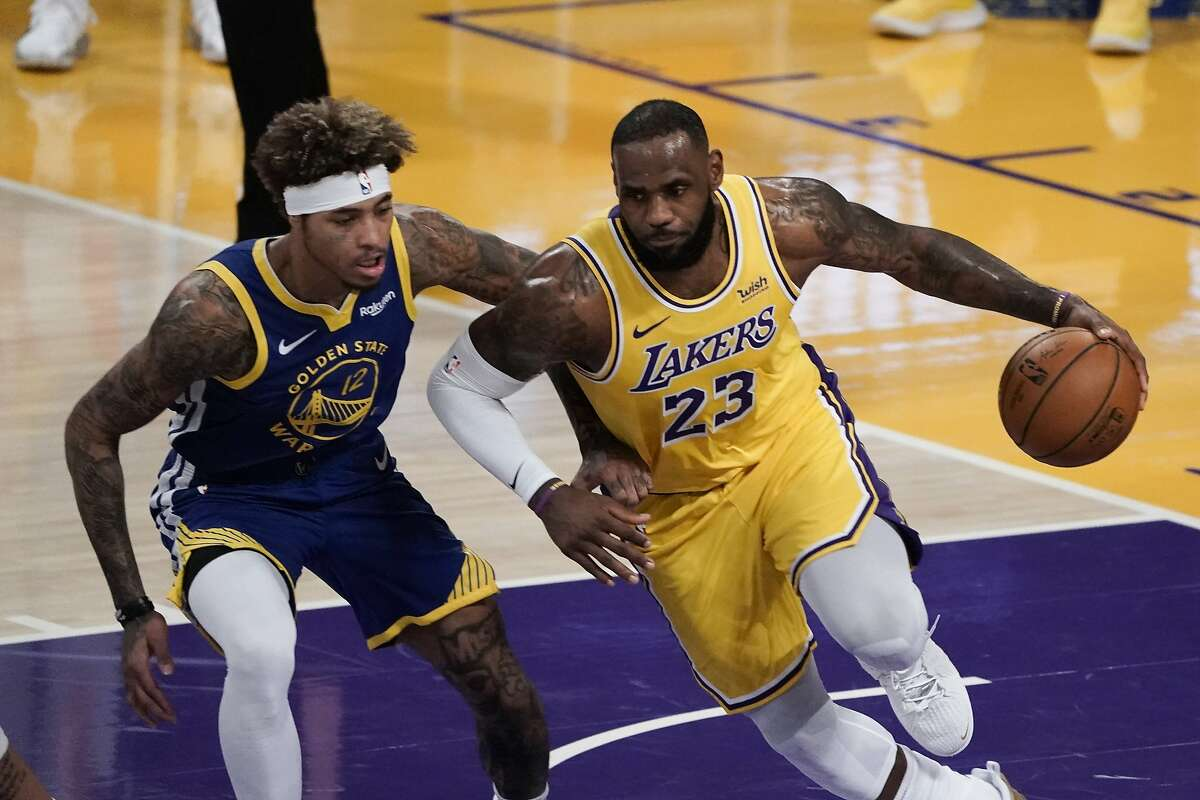 Los Angeles Lakers' LeBron James, right, dribbles past Golden State Warriors' Kelly Oubre Jr. during the first half of an NBA basketball game, Monday, Jan. 18, 2021, in Los Angeles.