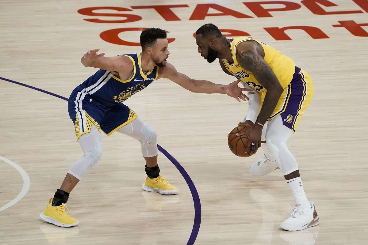 Golden State Warriors' Stephen Curry, left, pressures Los Angeles Lakers' LeBron James during the first half of an NBA basketball game, Monday, Jan. 18, 2021, in Los Angeles.