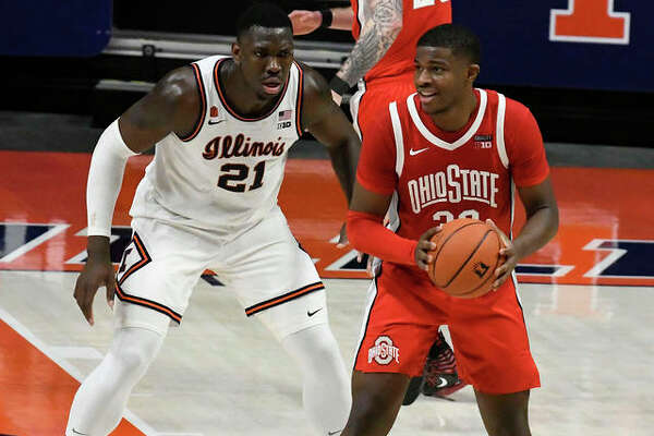 Ohio State's E.J. Liddell looks to pass as he is defended by Illinois' Kofi Cockburn (21) on Saturday in Champaign. Liddell, a former Illinois Mr. Basketball at Belleville West, scored 26 points in the Buckeyes win.
