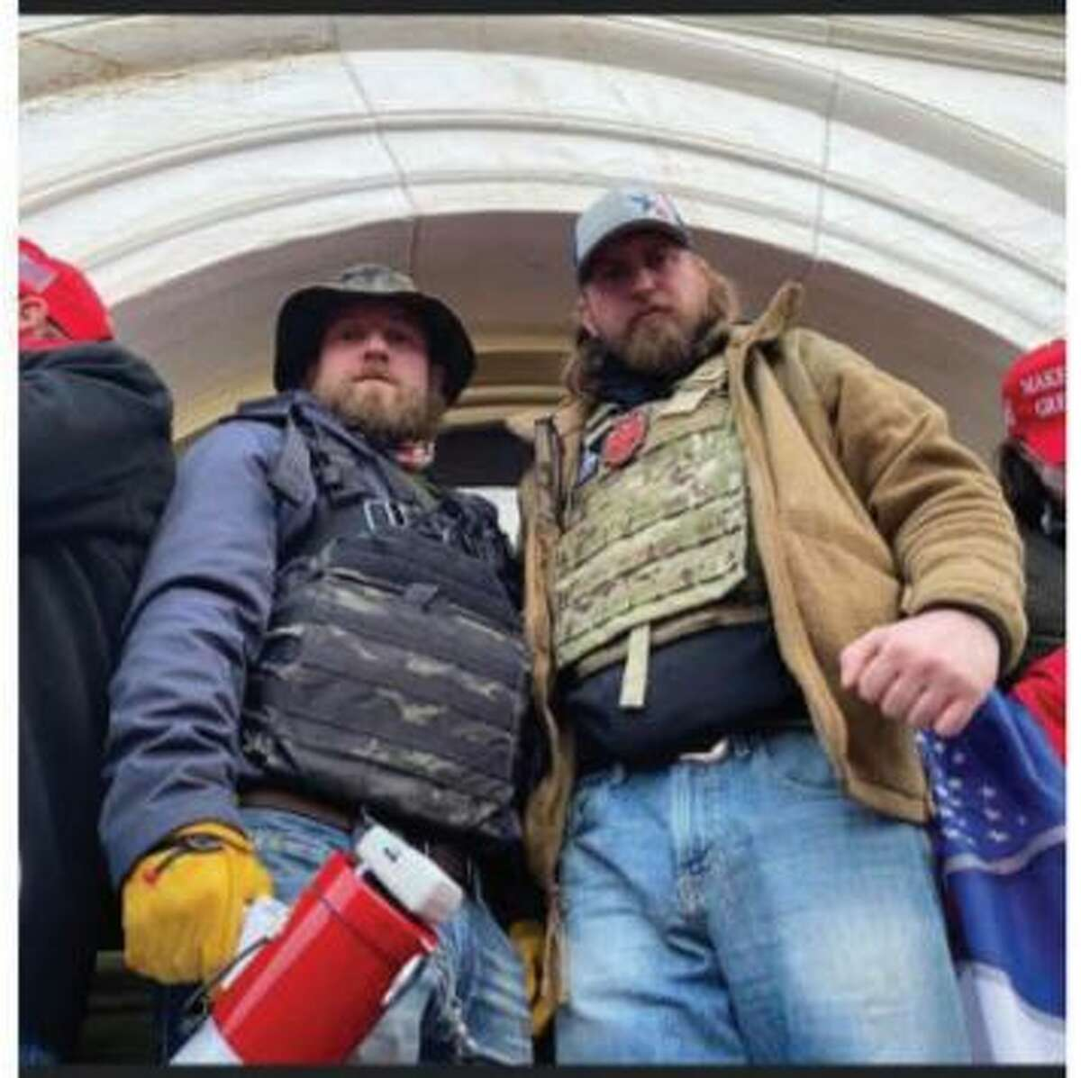 Ryan Nichols, left, and Alex Harkrider stand in front of a busted window at the U.S. Capitol with weapons and tactical gear during the Jan. 6 riot. Both East Texas men now face federal charges.