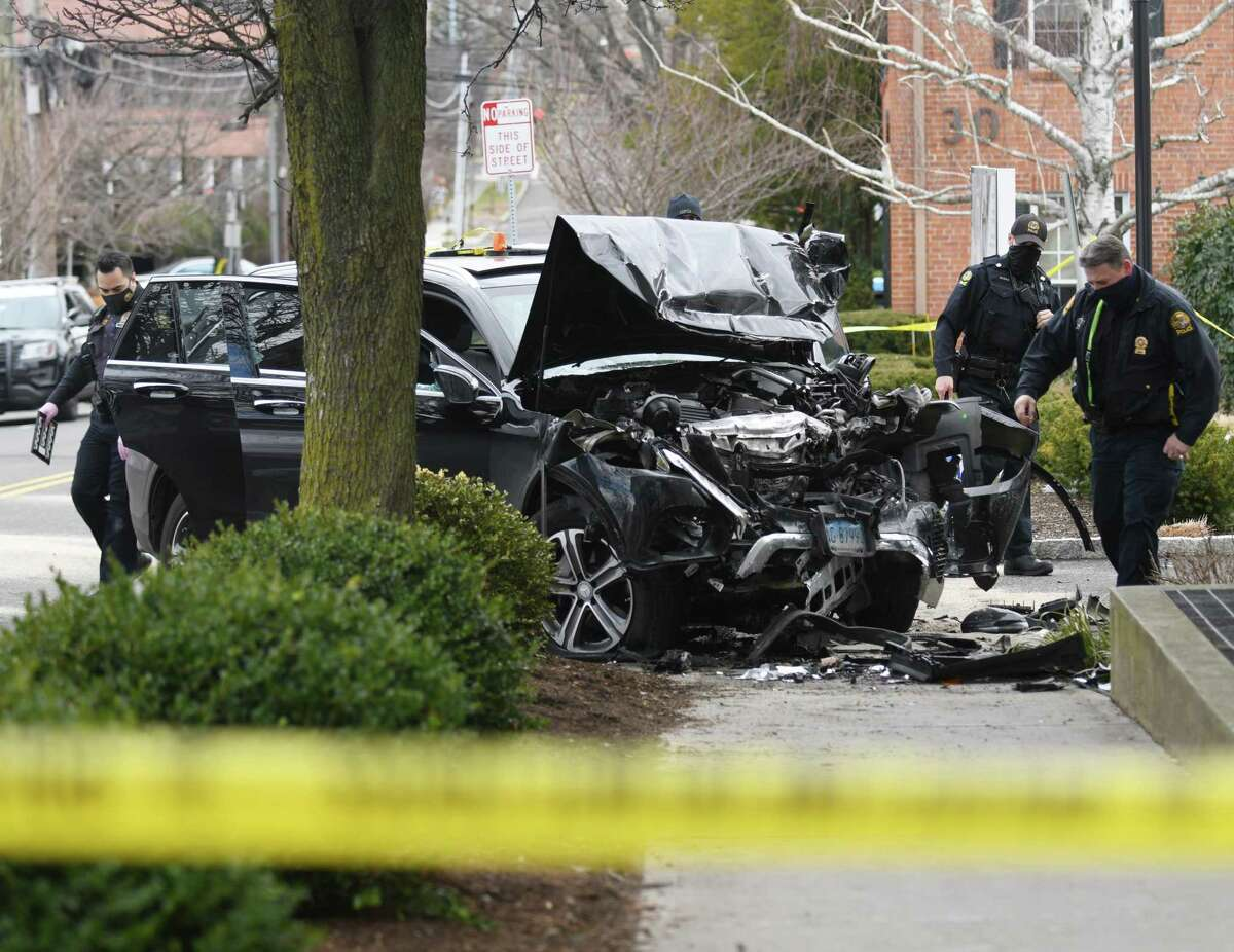 Greenwich Police examine the aftermath of a single car accident on East Elm Street on Tuesday.