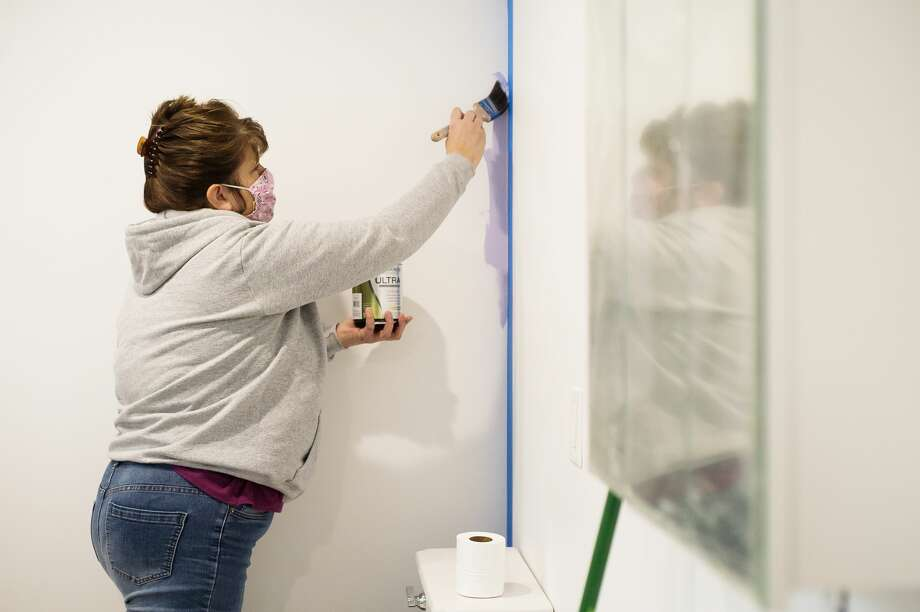 Angela Cole paints a wall in the home of Shelly Sampier Thursday, Jan. 14, 2021 in Sanford. While putting the finishing touches on the renovation, Sampier reached out to community leaders and asked them each to paint one wall in her home as a way to honor their support. (Katy Kildee/kkildee@mdn.net) Photo: (Katy Kildee/kkildee@mdn.net)