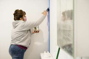 Angela Cole paints a wall in the home of Shelly Sampier Thursday, Jan. 14, 2021 in Sanford. While putting the finishing touches on the renovation, Sampier reached out to community leaders and asked them each to paint one wall in her home as a way to honor their support. (Katy Kildee/kkildee@mdn.net)