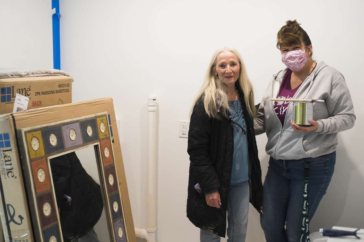 Shelly Sampier, left, and Angela Cole, right, pose for a photo Thursday, Jan. 14, 2021 at Sampier's home in Sanford. While putting the finishing touches on the renovation, Sampier reached out to community leaders and asked them each to paint one wall in her home as a way to honor their support. (Katy Kildee/kkildee@mdn.net)
