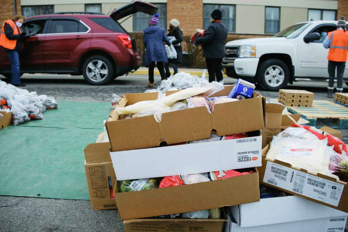 Volunteers load food bags and boxes into vehicles during a mass food distribution put on by Catholic Charities of the Diocese of Albany, and the Regional Food Bank of Northeastern New York at Macedonia Baptist Church on Tuesday, Jan. 19, 2021, in Albany, N.Y. (Paul Buckowski/Times Union)