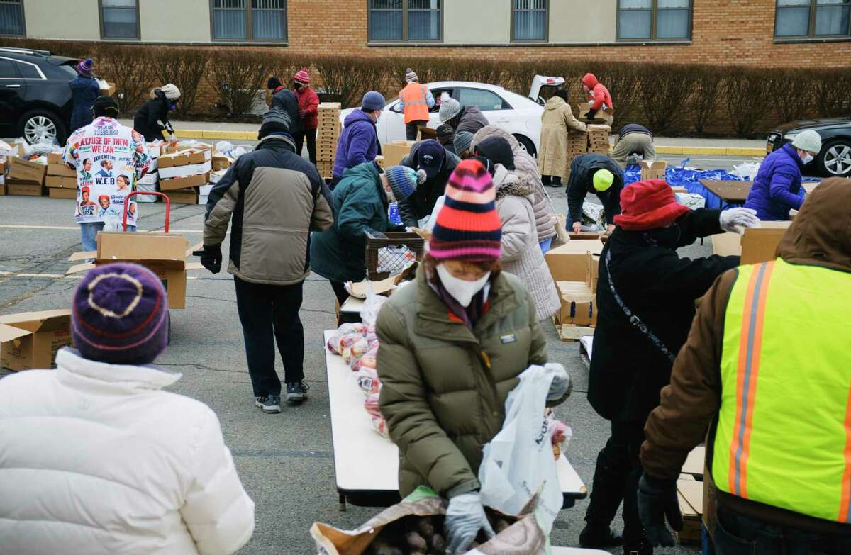 Volunteers pack food into bags and boxes for distribution to those in need during a mass food distribution put on by Catholic Charities of the Diocese of Albany, and the Regional Food Bank of Northeastern New York at Macedonia Baptist Church on Tuesday, Jan. 19, 2021. (Paul Buckowski/Times Union)