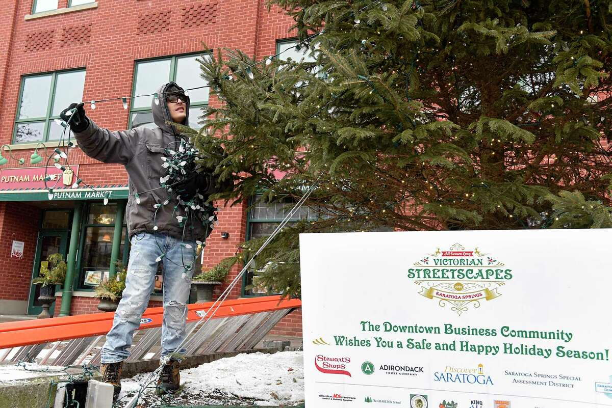 Preston Roberts of The Christmas Guys takes off a string of lights as he and his co-workers take down a Christmas Tree on Broadway on Tuesday, Jan. 19, 2021 in Saratoga Springs, N.Y. (Lori Van Buren/Times Union)