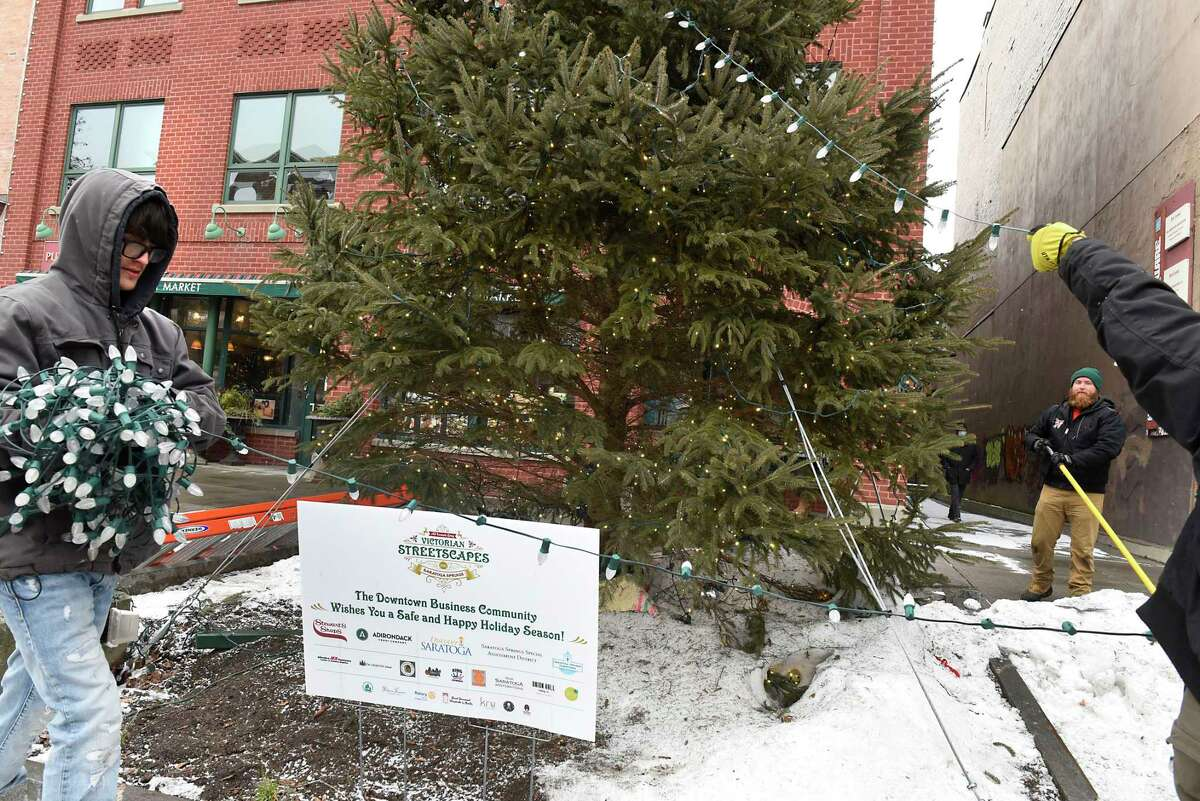 Preston Roberts, left, and Ron Crowley, second from right, of The Christmas Guys work to take down a Christmas Tree on Broadway on Tuesday, Jan. 19, 2021 in Saratoga Springs, N.Y. (Lori Van Buren/Times Union)