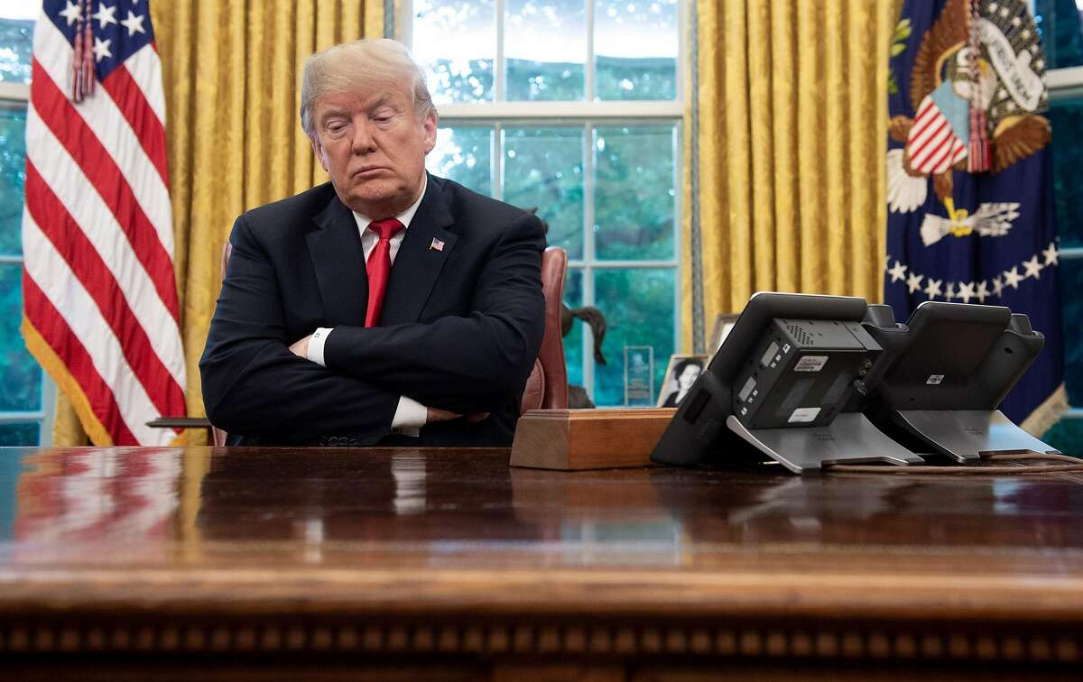 President Trump at the Resolute desk in the White House in 2018 - opinions differ on whether the Senate can try him once he's out of office.