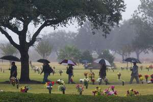 """Mourners cross the Grand View Memorial Park on their way to the Grand View Funeral Home for the funeral of brothers Robert Tisnado, 39, and Gilbert """"Gibby"""" Tisnado, 48, who died in a hazardous chemical leak at a DuPont plant in La Porte last week Friday, Nov. 21, 2014, in Pasadena. ( Johnny Hanson / Houston Chronicle )"""