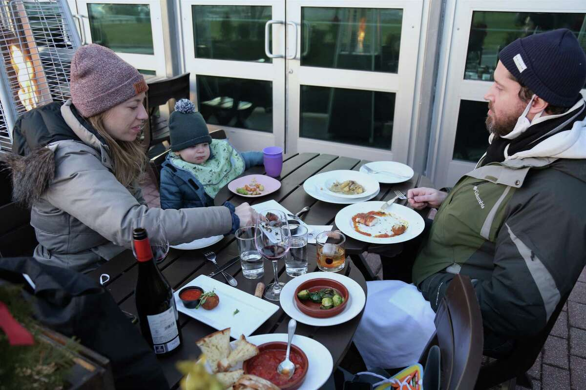 The Henshaw-Lynch family of Brooklyn, N.Y., enjoys an early dinner at Basso Restaurant & Wine Bar on Monday, Jan. 18, 2021, in Westport, Conn.