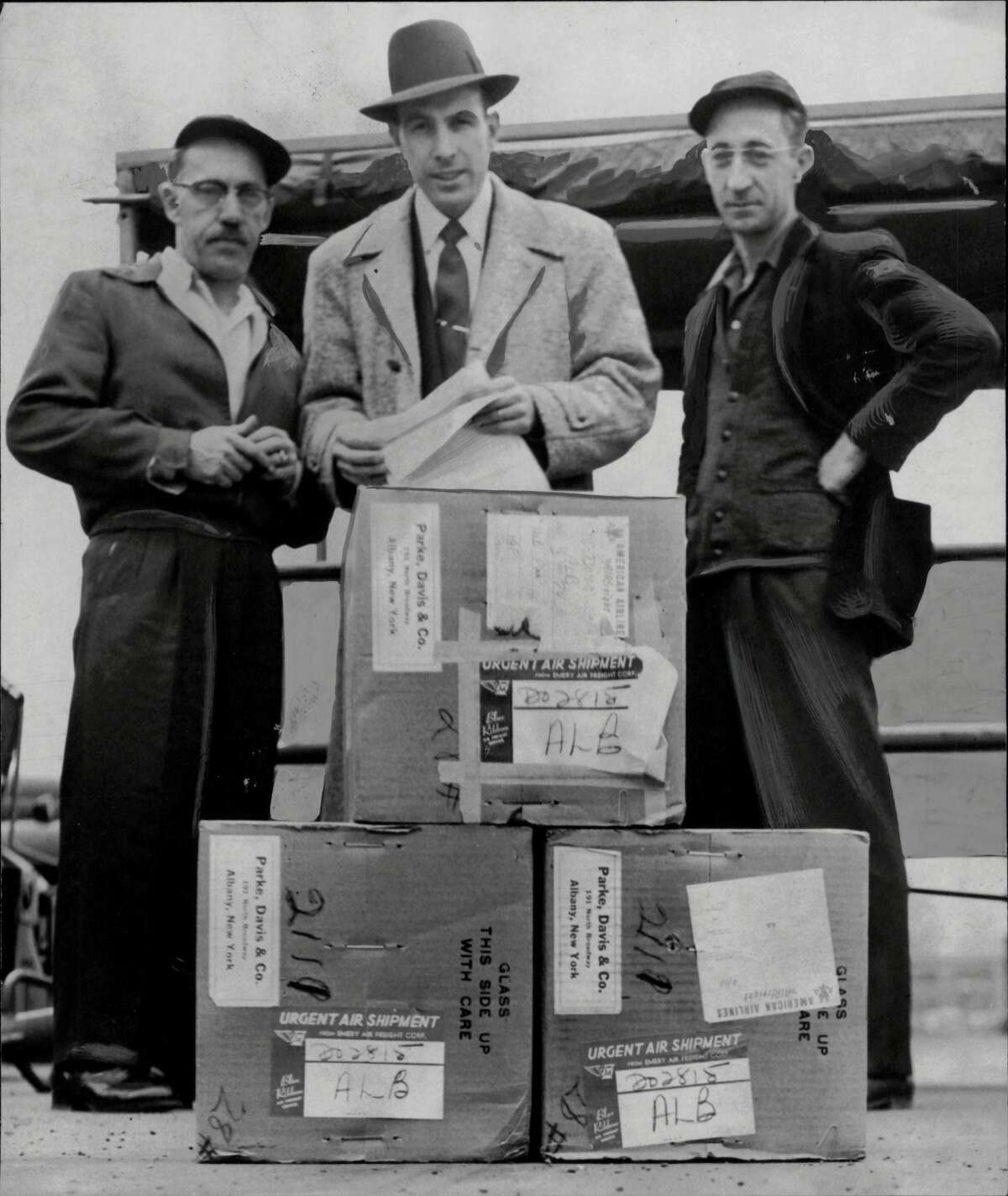 Salk Vaccine Arrives In Albany - The first commercial shipment of Salk polio vaccine arrived at Albany Airport consigned to Parke Davis & Company, 191 Broadway, Menands. The vaccine company officials said, will be distributed to druggists and physicians through regular channels. Shown receiving the shipment of three cases at the airport, left to right, are: Joseph Van Winkle, delivery agent; John V. Healy, manager of the Albany office of the Emery Air Freight Corporation, and Bernard Van Winkle, delivery agent. April 13, 1955 (Knickerbocker News Staff Photo/Times Union Archive)