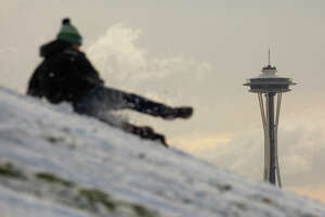 SEATTLE, WA - FEBRUARY 09: The Space Needle is pictured in the background as a man sleds at Gas Works Park after a large storm blanketed the city with snow on February 9, 2019 in Seattle, Washington. (Photo by David Ryder/Getty Images)