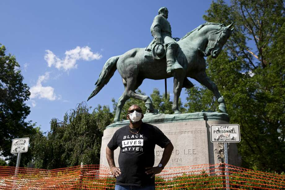Don Gathers stands in front of a statue depicting Robert E. Lee during a racial justice protest in Charlottesville on May 30, 2020. It happened fives days after George Floyd died in police custody on May 25. Photo: RYAN M. KELLY/AFP Via Getty Images
