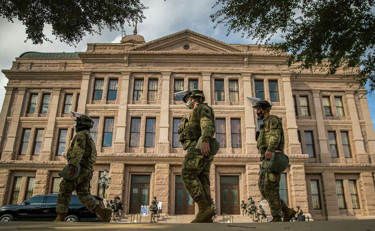 The National Guard and DPS state troopers and protect the Capitol grounds on the first day of the 87th Legislature, Tuesday Jan. 12, 2021 in Austin, Texas. More than 100 Texas troopers, including dozens wearing tactical vests and carrying riot gear, stood on guard outside the state Capitol on Tuesday as lawmakers returned to work amid FBI warnings of armed protests at statehouses across the country. (Ricardo B. Brazziell/Austin American-Statesman via AP)