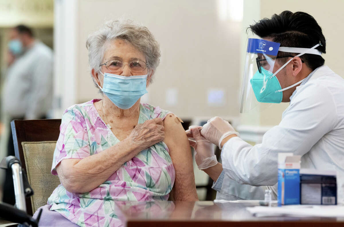 A CVS pharmacist gives the Pfizer/BioNTech COVID-19 vaccine to a resident at the Emerald Court senior living community in Anaheim, Calif., on Friday, Jan. 8, 2021.