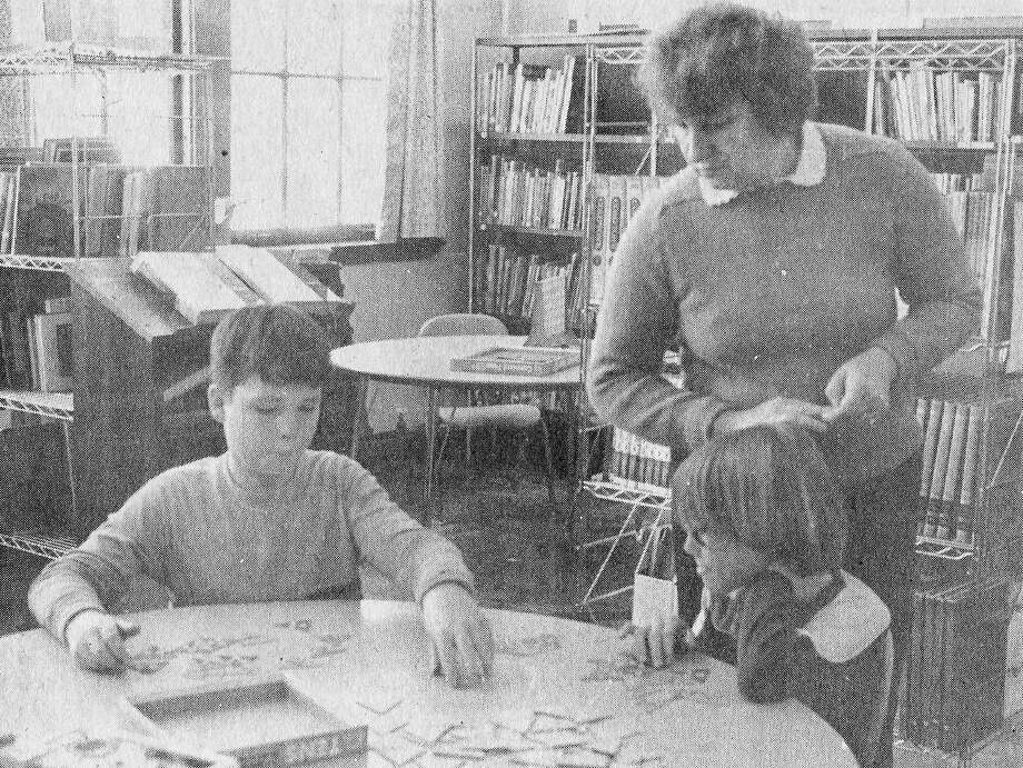 """From the Jan. 20, 1981 issue of the Manistee News Advocate, Washington Elementary fifth graders Ricky Field (left) and Brian Ellen concentrate on a game called """"Tens"""" while educator Marge Hornkohl looks on. """"Tens"""" and other educational games were purchased for Washington, Jefferson and Lincoln schools by the Manistee Jaycettes for student use. (Manistee County Historical Museum photo)"""